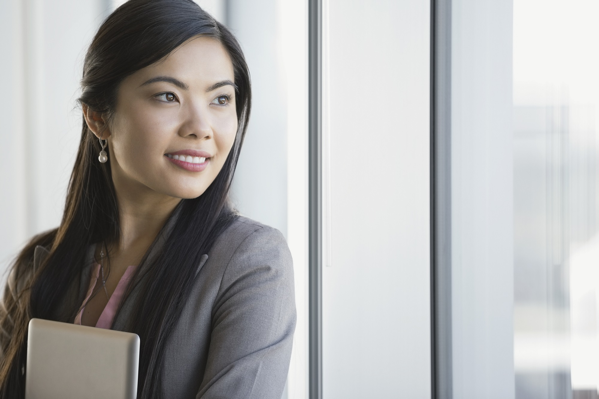 05 Apr 2014 --- Smiling businesswoman looking out office window --- Image by © Hero Images Inc./Hero Images Inc./Corbis