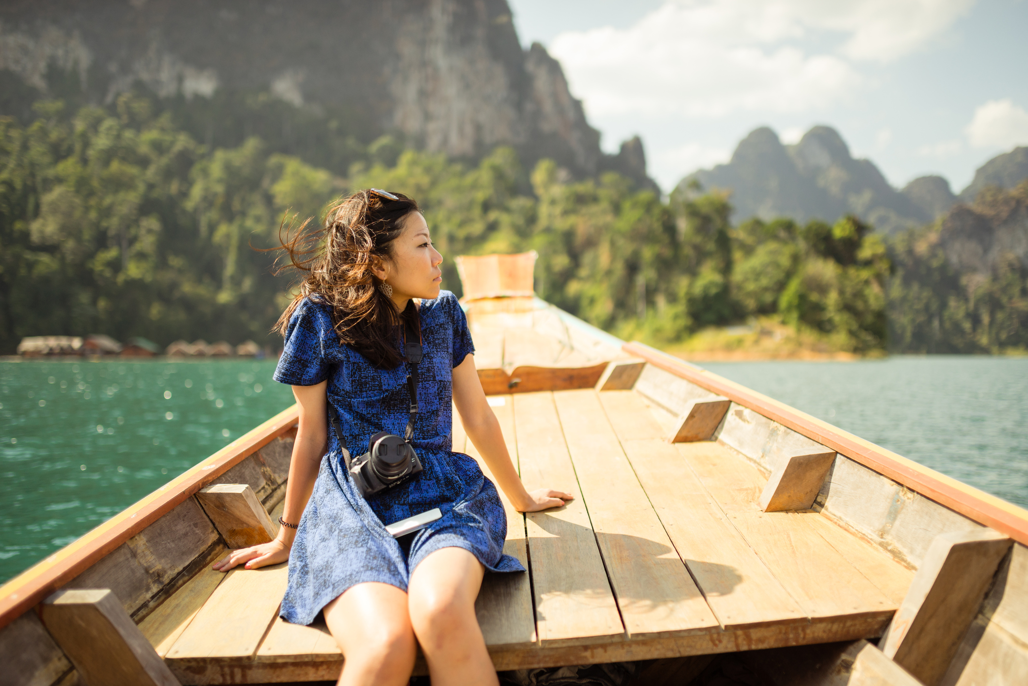 Asian girl wearing blue dress travelling on a longtail boat in Cheow Lan Lake, Khao Sok national Park, Thailand.