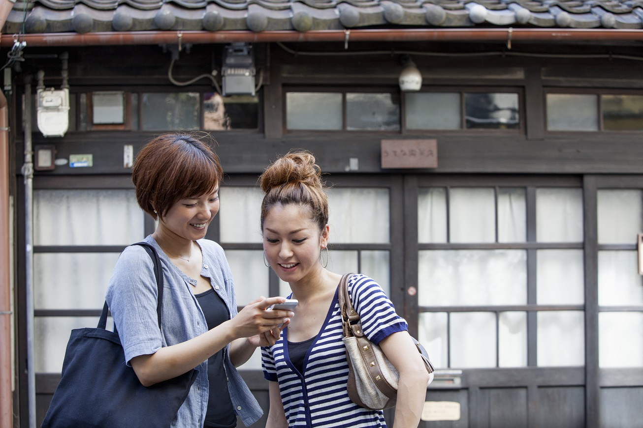 14 Aug 2013, Osaka, Japan --- Two women standing outdoors, looking at cellphone. --- Image by © Liesel Bockl/Mint Images/Corbis