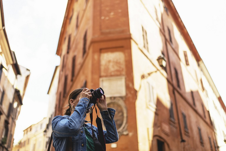 Female brunette tourist photographing streets of an italian city.