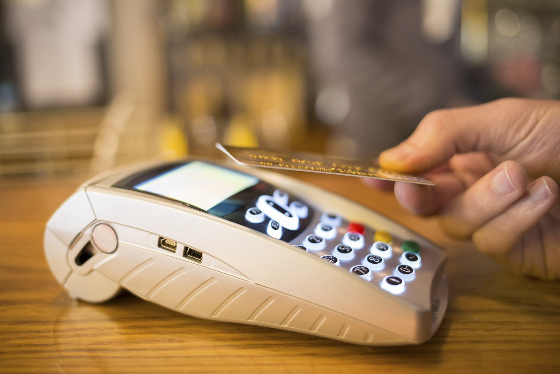 Man paying with NFC technology on credit card, restaurant, shop