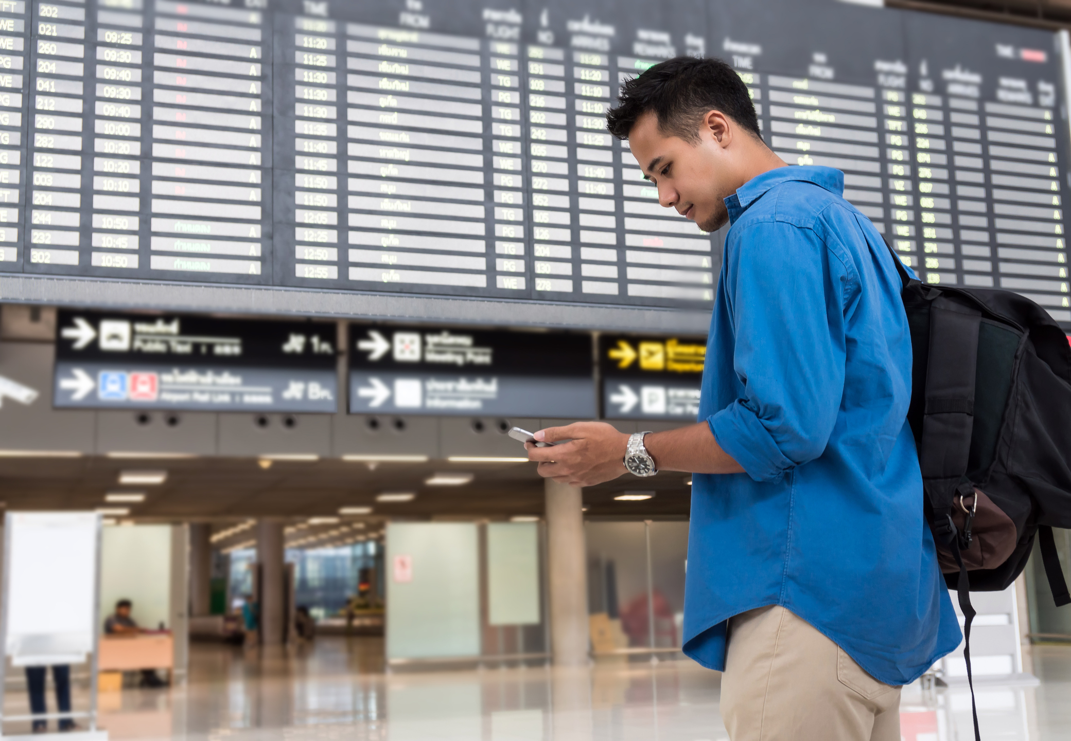 Asian traveler using the smart mobile phone for check-in at the flight information screen in modern an airport, travel and transportation with technology concept.
