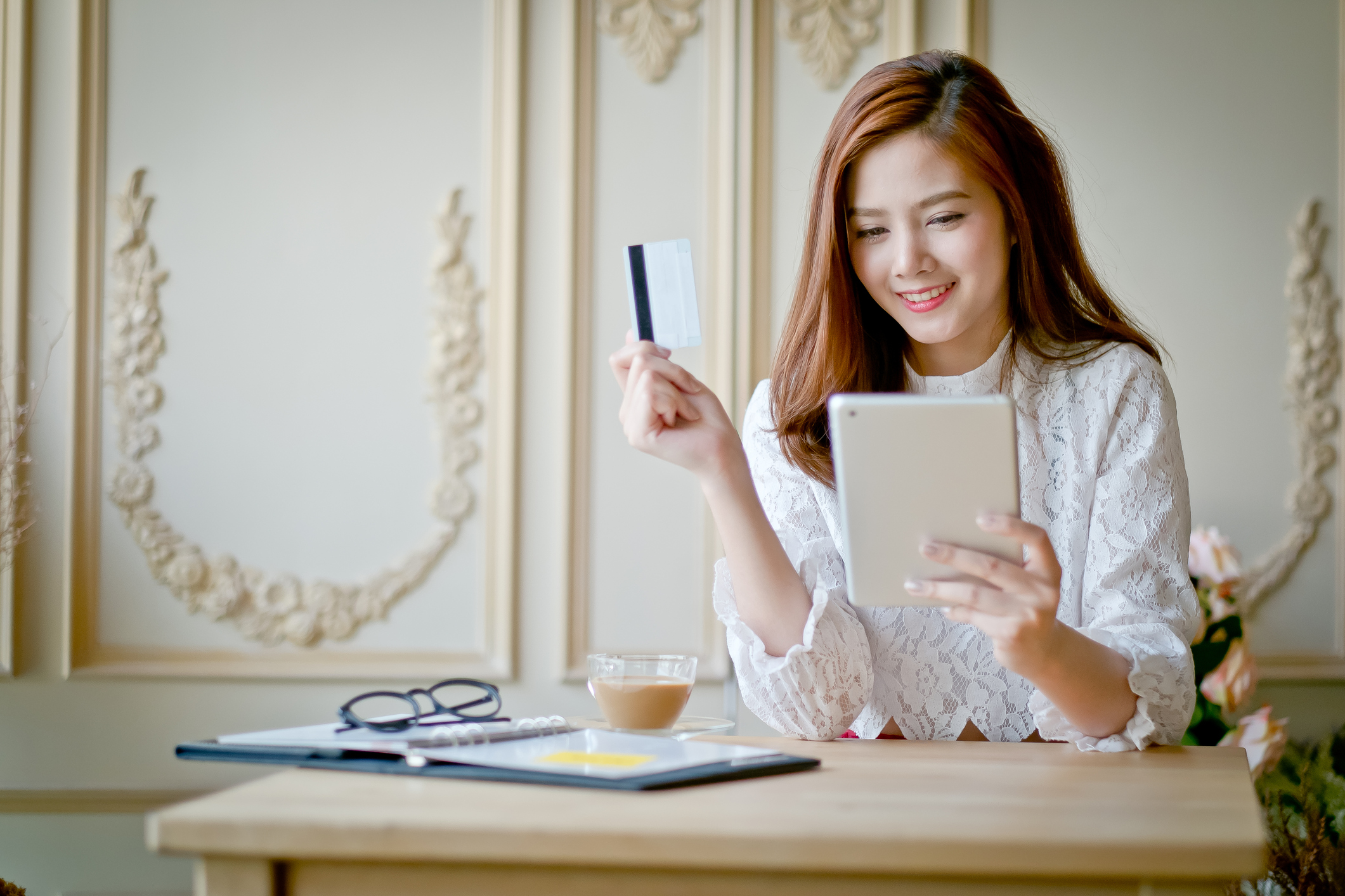 Happy woman shopping online, holding credit card, using tablet computer, electronic purchase.