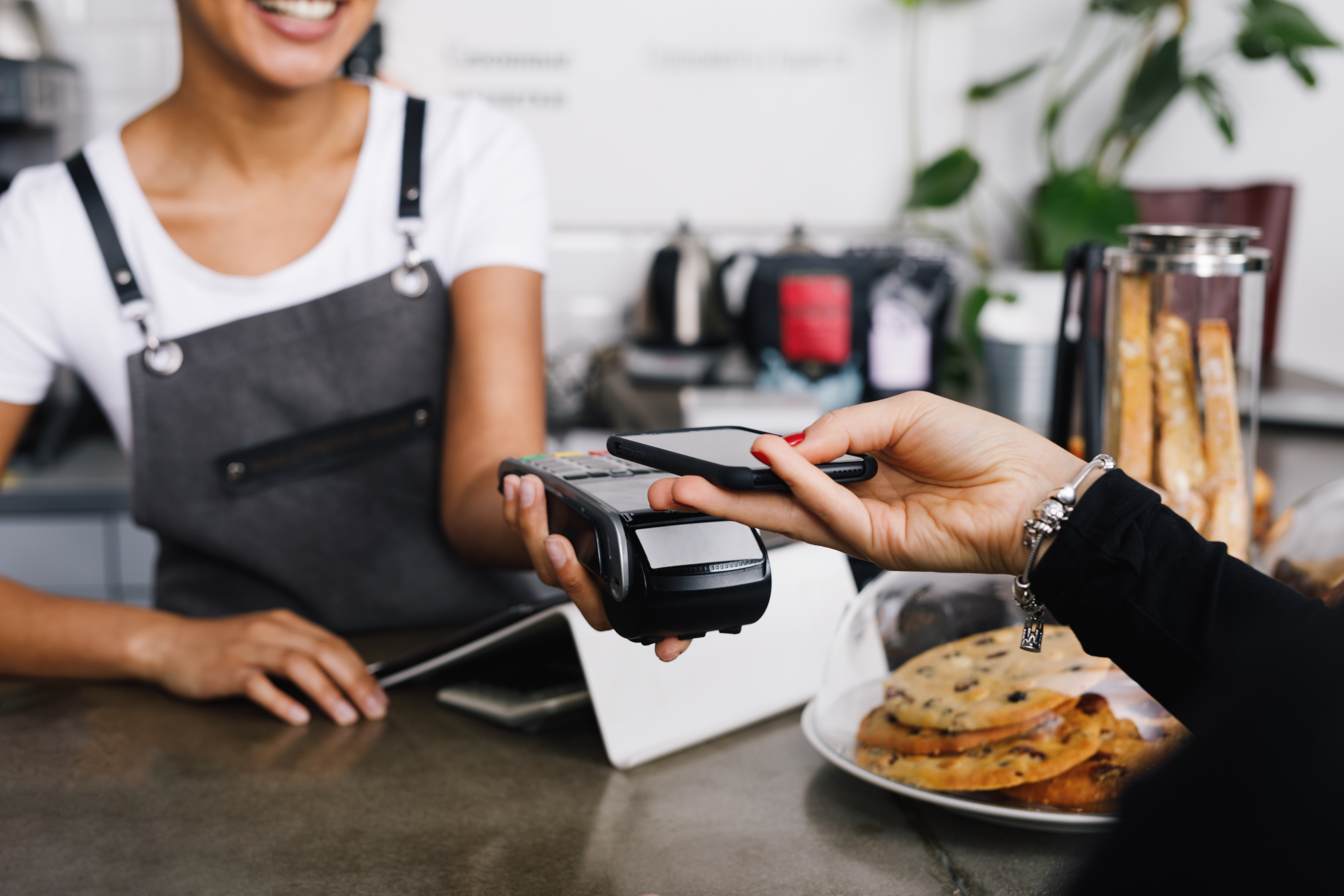 Customer making wireless payment using smartphone in cafe