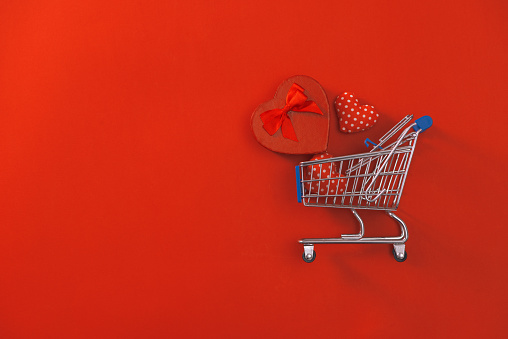 Shopping trolley with gift box on red background. Valentine's Day shopping and sale.