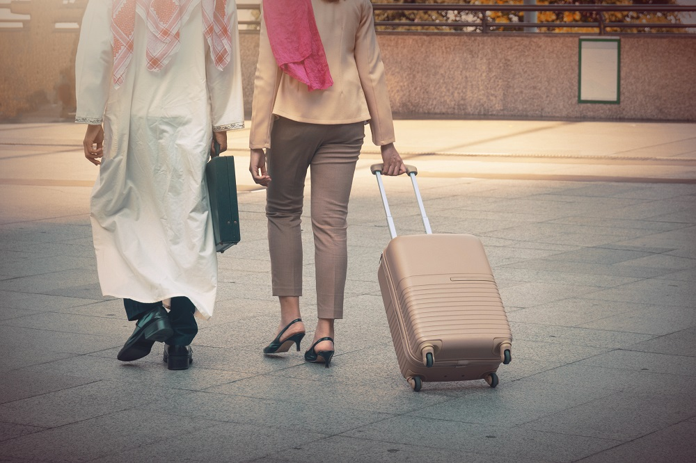Arab man and woman walking carrying a suitcase