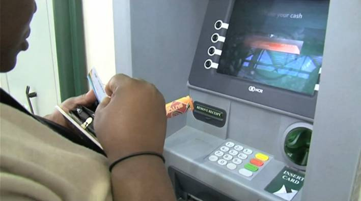 Flickr Photo: A SASSA grant recipient using her card withdraw cash from an ATM