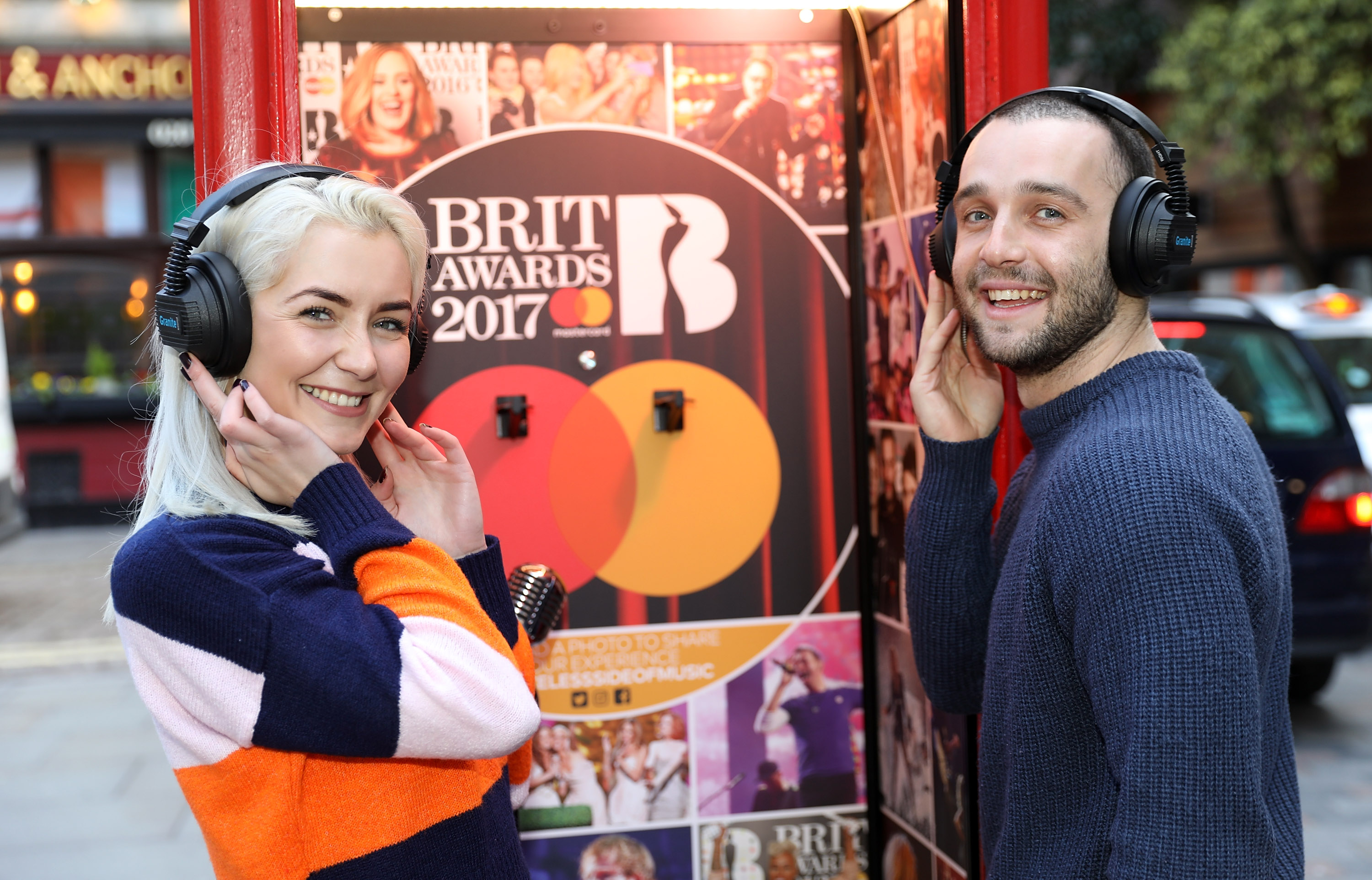 LONDON, ENGLAND - FEBRUARY 20:  Two members of the public enjoying the Mastercard BRITs Listening Booth which launched today in Covent Garden in celebration of The BRIT Awards 2017 on February 20, 2017 in London, England.  Open to the public today and tomorrow, the booth will then travel to the Awards Show which takes place on February 22nd at London's 02 Arena.  (Photo by Tim P. Whitby/Getty Images for Mastercard)