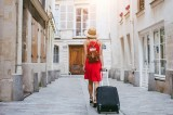 travel background, woman tourist walking with suitcase on the street in european city, tourism in Europe