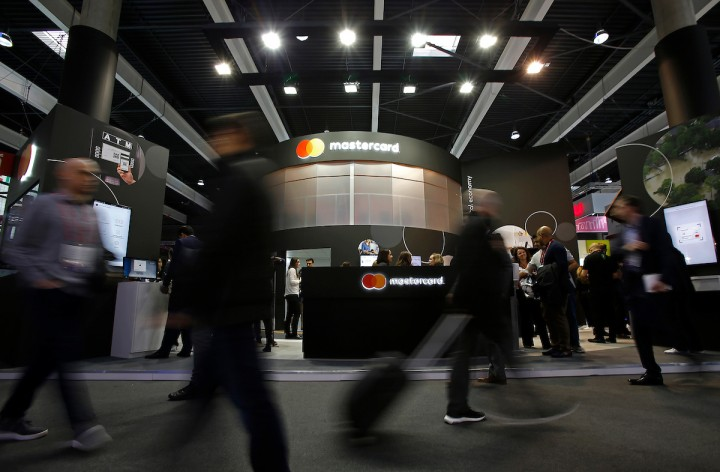 IMAGE DISTRIBUTED FOR MASTERCARD - Visitors walk past the Mastercard booth at the 2018 Mobile World Congress on Monday, Feb. 26, 2018 in Barcelona, Spain. (Manu Fernandez/AP Images for Mastercard)