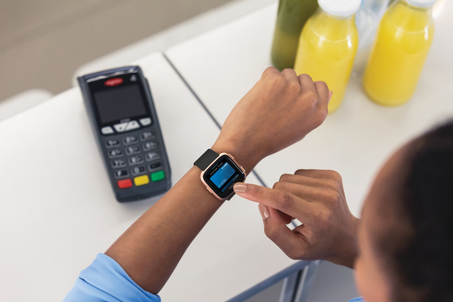 Lifestyle photo of young black female with versa showing Fitbit pay