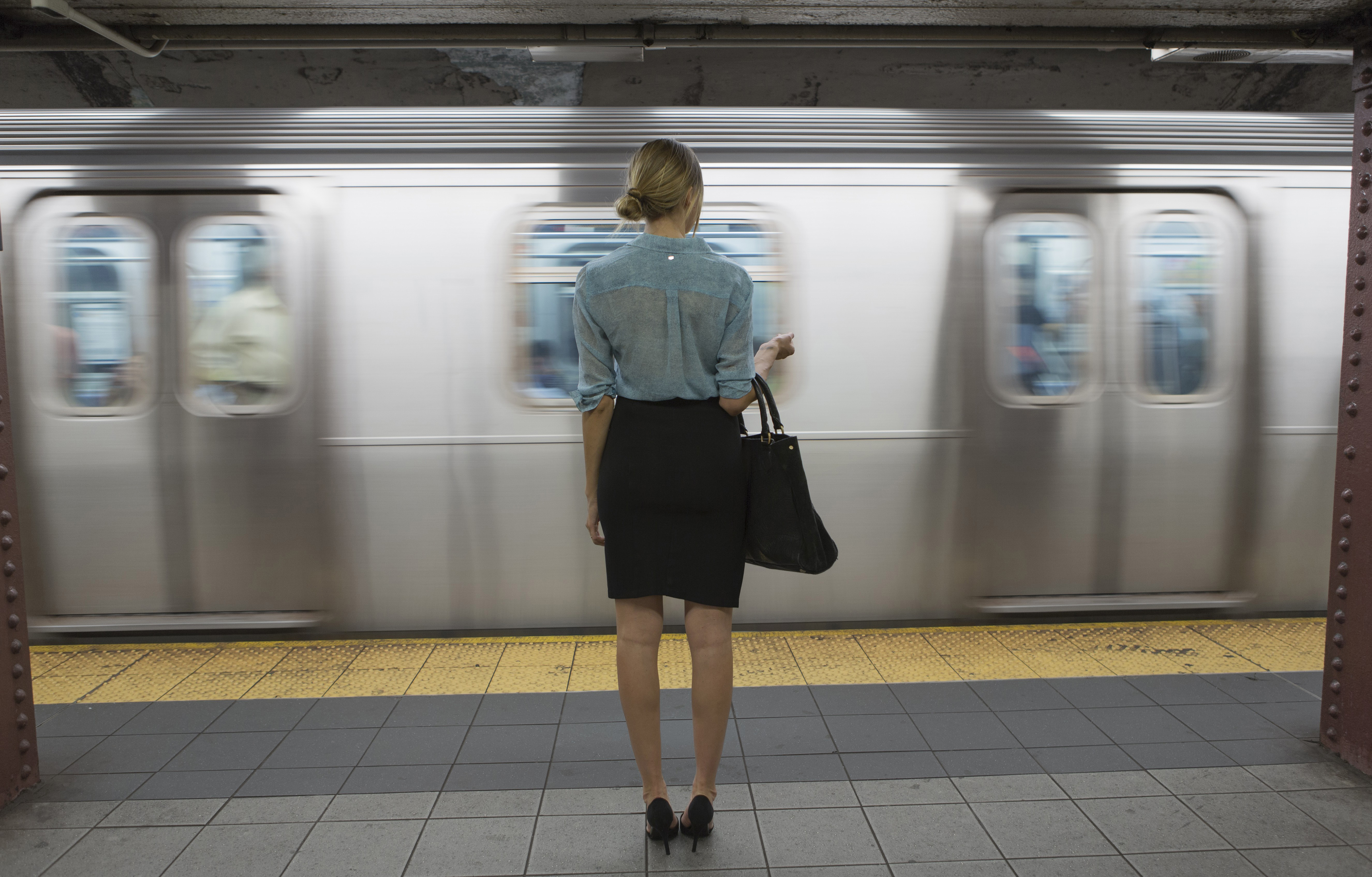 29 Jul 2014 --- Caucasian woman standing near passing subway in train station --- Image by © Blend Images/Corbis