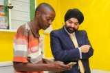 Ajay Banga, Mastercard president and CEO (right), discusses the benefits of mobile payments with Paul Makuleke, owner of Kasi Convenience Food and Internet Café in Alexandra, Johannesburg. Makuleke is one of thousands of informal traders who can now use Masterpass, the digital payment service from Mastercard, to pay electronically for stock ordered from the free Spazapp android app, and accept cashless payments from their customers - using their mobile phones.