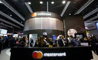 IMAGE DISTRIBUTED FOR MASTERCARD - Visitors walk past a Mastercard booth at the 2018 Mobile World Congress on Monday, Feb. 26, 2018 in Barcelona, Spain. (Manu Fernandez/AP Images for Mastercard)