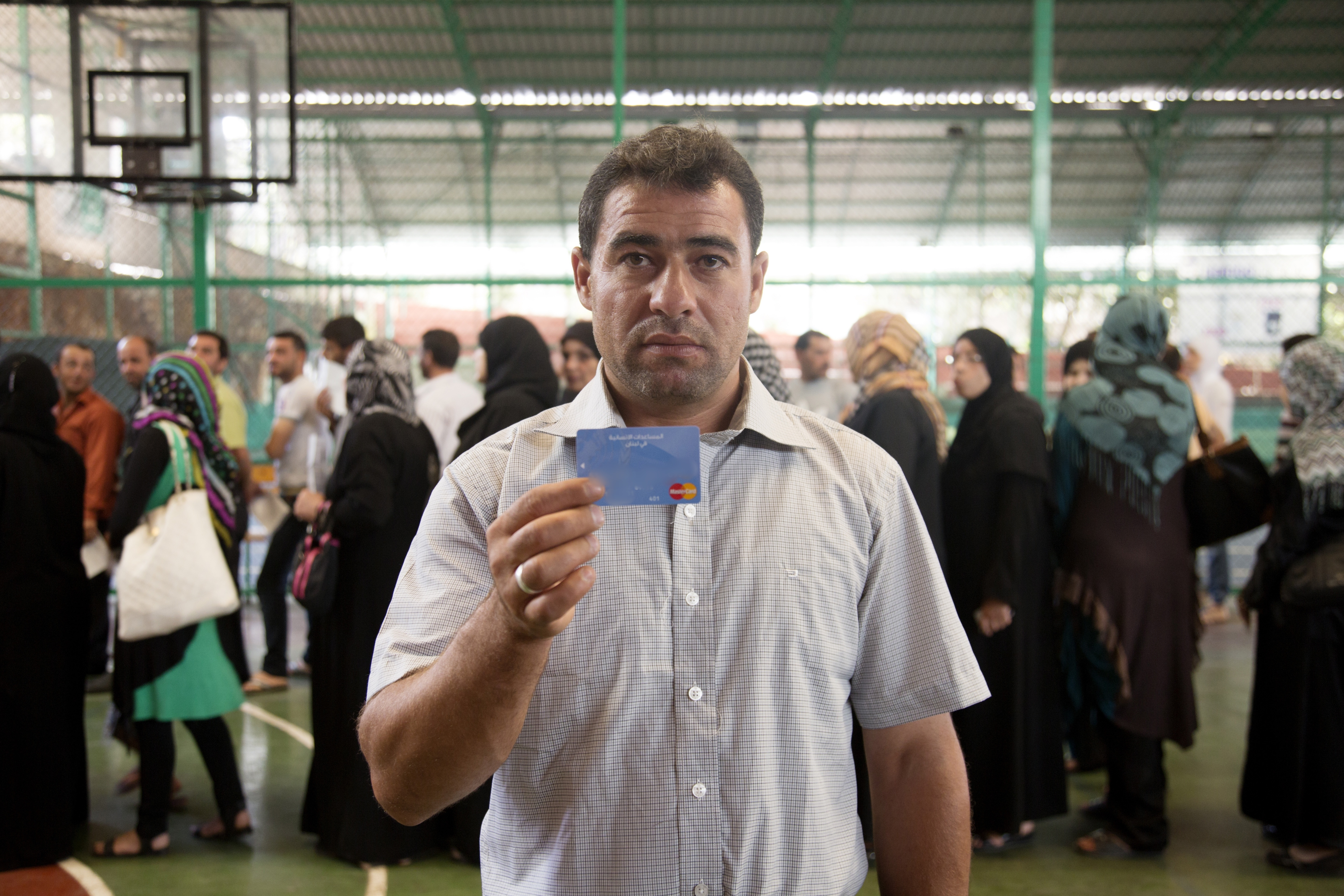 Syrian refugee Ali Ahmad Farhat holds his MasterCard / WFP e-card as others stand in line to receive theirs, at a basketball court