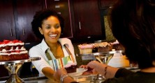 African American bakery owner serving customer cupcake