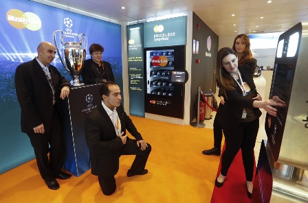 Priceless: visitors to the MasterCard booth take a photo wth the UEFA Champions League trophy at the Mobile World Congress on Tuesday, Mar. 03, 2015 in Barcelona. (Marce Martinez/AP Images for MasterCard)