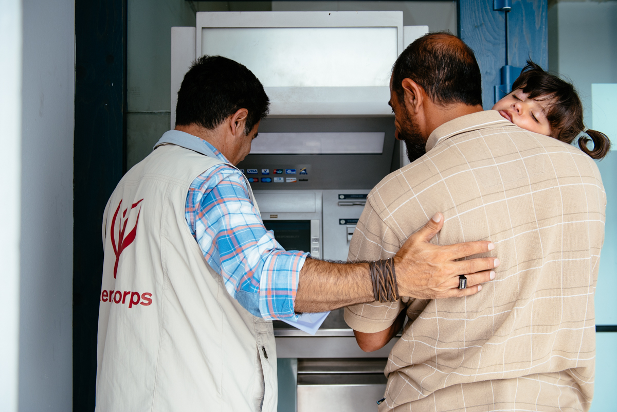"2016 May, Mytilene, Lesvos, Greece. Following the issue of a cash distribution debit card, Reza, a Mercy Corps team member helps Ahmed, 38, withdraw cash from an ATM since the ATMs only operate in Greek and English here. Ahmed, his wife Wala'a, 30, and their three children fled their hometown of Der Azour around the new year. Ahmed recalls that when ISIS took over Der Azour, they began implementing strict rules. The family stuck it out, however, until air strikes destroyed their home. Wala'a was 8 months pregnant at the time.  It took the family five tries – starting 1/5/16 – to get across from Turkey to Greece. While they waited for their chance to cross, Wala'a gave birth to their son, Abubakkar. They finally crossed successfully on 4/4. ""Our lives have become soap operas,"" says Ahmed wistfully. He says the baby is healthy, but has not yet seen a doctor for a check up or first immunizations. Mercy Corps provides cash distributions to Ahmed and other refugee families living in the camps for the most vulnerable in Lesvos. For refugees facing an uncertain future, unclear whether they will be allowed to remain in Europe or be deported to Turkey, this cash is a critical resource that helps them meet their most urgent needs.  Ahmed's mother is also traveling with the family. She has diabetes and heart disease and is unable to get medical treatment. Ahmed says they'll use the money from the cash distribution mainly to buy medicine and some clothing the children need."