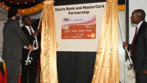 Ajay Banga, President and CEO MasterCard Worldwide (left), Dr. James Mwangi, CEO Equity Bank Group (left) and Professor Njuguna Ndung'u, Governor Central Bank of Kenya, unveil a mockup of the new EMV card to be rolled out as a result of the partnership between Equity Bank and MasterCard Worldwide. As part of the collaboration, MasterCard debit and prepaid cards with chip-enabled technology will be issued, first into the Kenyan market and then extended into Uganda, Tanzania, Rwanda, and South Sudan. The cards will also introduce MasterCard PayPass™ with the first ever installation of PayPass enabled point of sale terminals across the region.