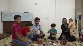 Family lunch at the apartment of Syrian refugee Ali Ahmad Farhat with food bought with his new electronic card